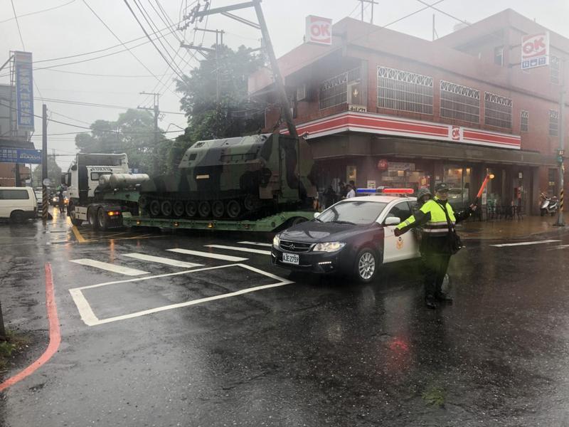 拖板車司機載送坦克時,不慎勾倒一旁電桿。(翻攝畫面)