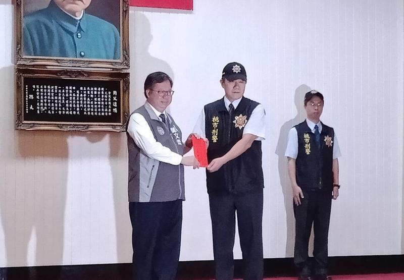 桃園市長鄭文燦頒獎給王姓小隊長。(翻攝畫面)