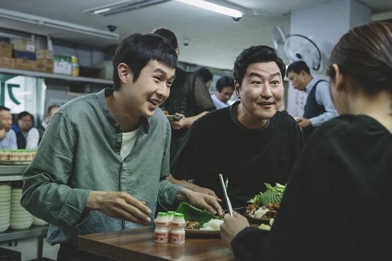 宋康昊(右)在《寄生上流》飾演無業遊民,崔宇植飾演的長子偽造學歷當家教,繼而引發一連串事件。(翻攝自Naver)