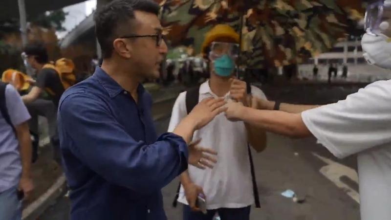 一名美國CBS電視台記者在前線報導時,身上沒有帶任何防護配備,示威者見狀送上雨傘和頭盔。(翻攝Ramy Inocencio推特)