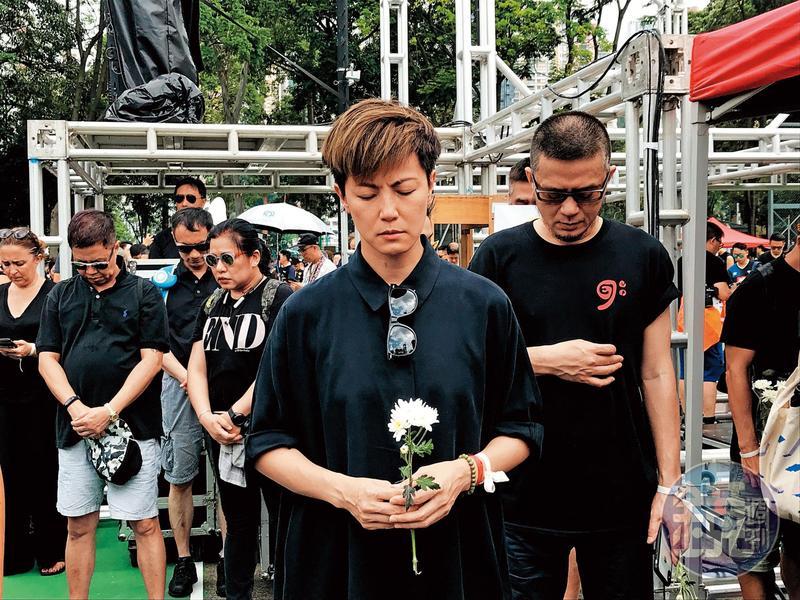 遊行起步前,民陣希望在場民眾為前日墜樓過世的抗爭者默哀,何韻詩手持白花、神情肅穆,右後為同樣勇於表態的藝人黃耀明。(陳怡靜攝)