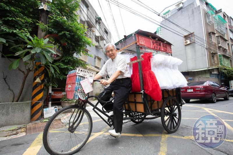林哲慧以三輪車載著自己手作的小禮服已超過20年,圖中的紅色禮服是他做給孫女穿的