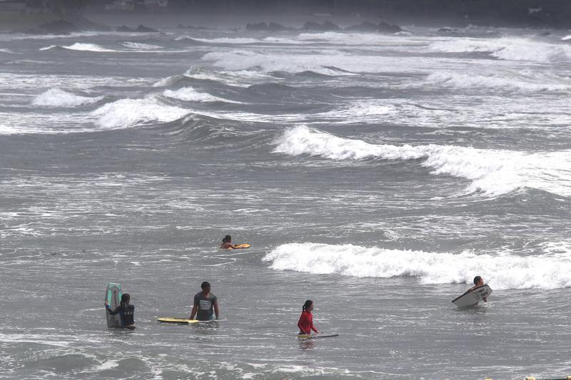 颱風天仍有不少人不顧海巡與警察勸阻,硬要到海邊衝浪。(東方IC)