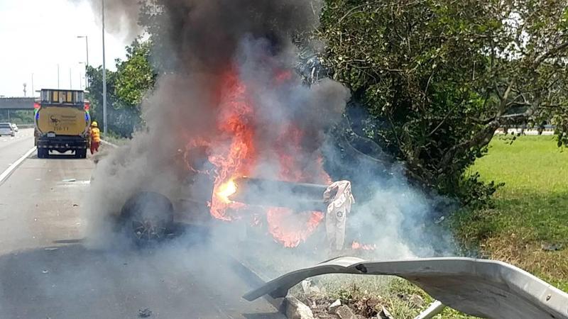 小客車自撞護欄後起火燃燒。(翻攝畫面)