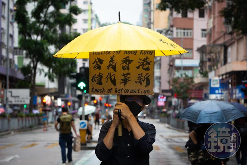 光復紅土遊行下著雷雨,民眾舉著抗議標語。