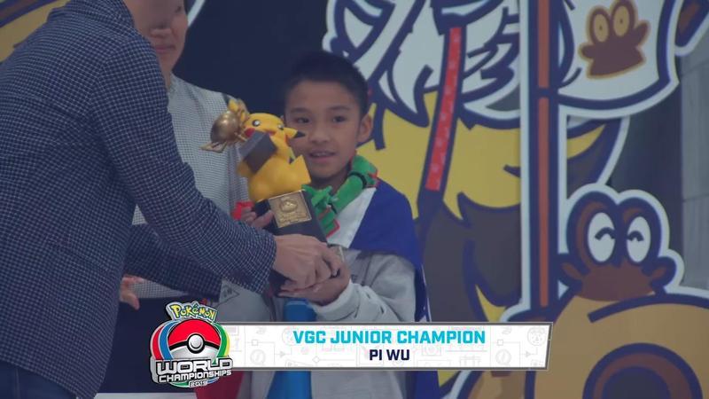 台灣10歲少年吳比奪下寶可夢世錦賽兒童組冠軍,身披國旗上台領取皮卡丘獎盃。(翻攝自「The Official Pokémon YouTube channel」Youtube頻道)