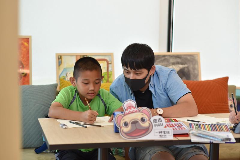 三位知名貼圖畫家與受兒福資助的六位孩童共同創作公益貼圖,雙方從忐忑到熟悉,留下珍貴情誼。圖為畫家一神與孩子奕程共畫貼圖。(LINE提供)