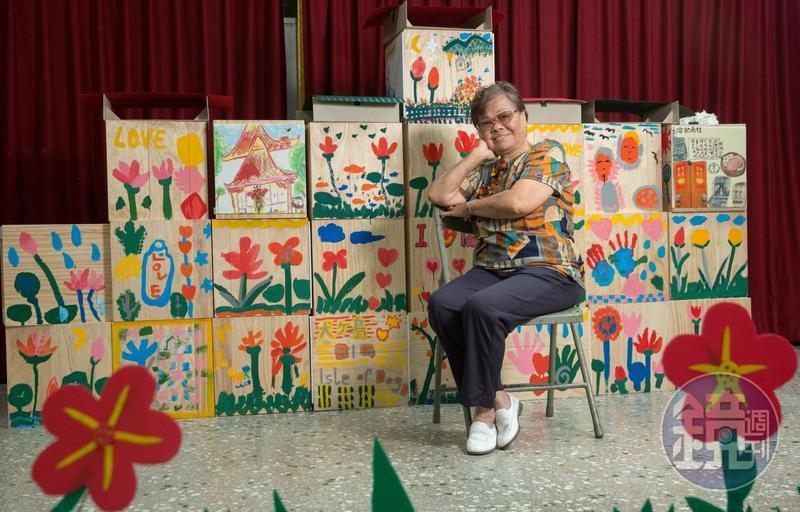 侯秀絨性格活,年輕時就愛拍照,當我們拿起相機時,她就很自然擺起姿勢,背景是下城社區做社區歷史記憶,由居民共同創作的畫。