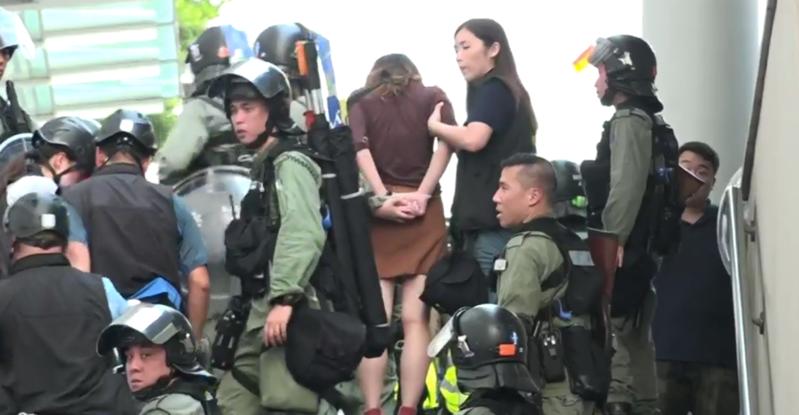 示威女大生因向警方丟擲飲料被捕,昨日獲保釋。(翻攝香港電台直播畫面)