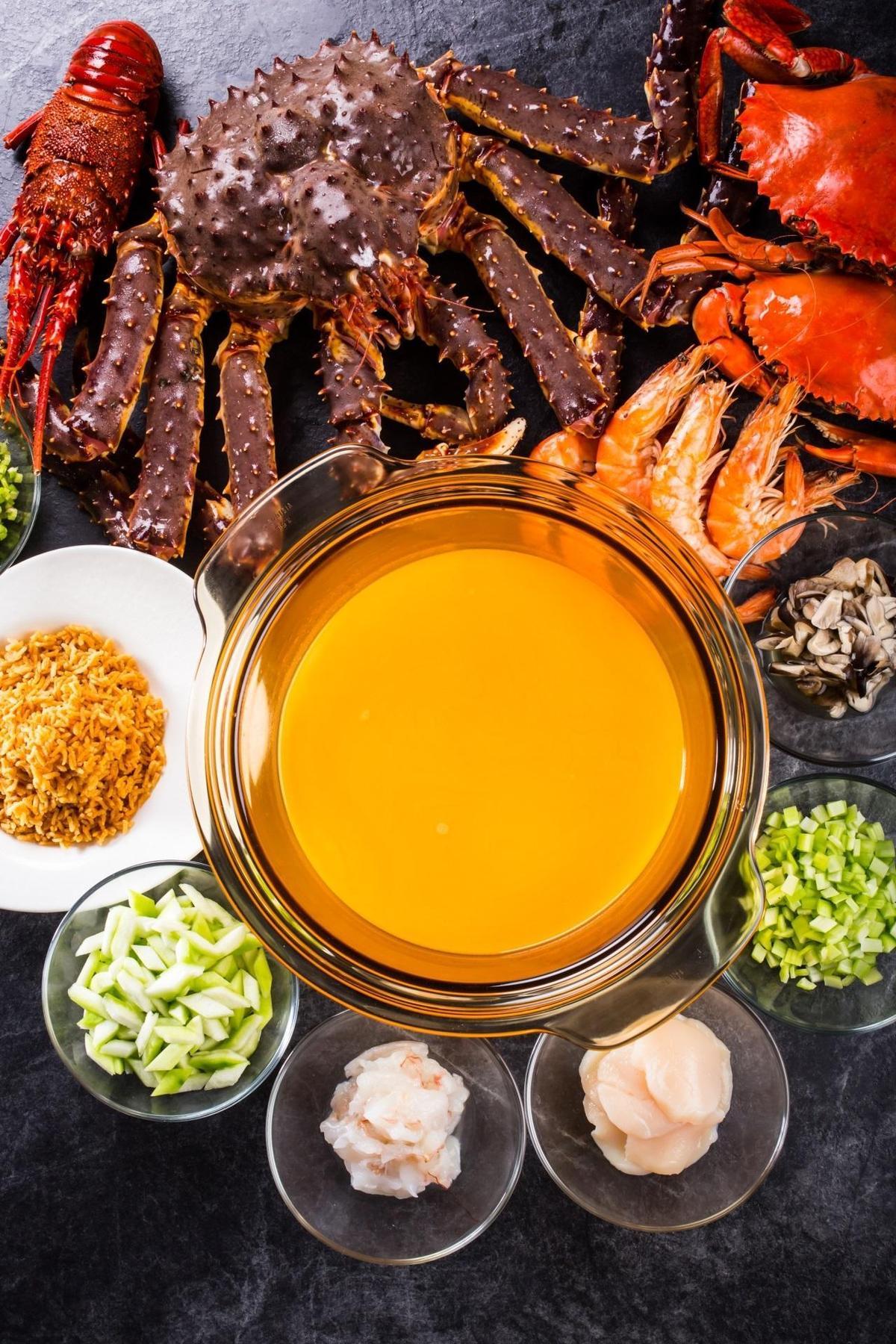 粉橘色高湯是以龍蝦、蟹殼、白蝦熬煮的精華海味。(台北晶華酒店提供)