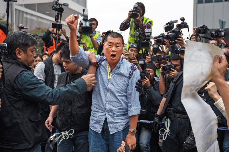 2014年12月11日,占中行動遭到警方強行清場,黎智英堅持在港島金鐘占領區內留守,當他遭警員押走時,仍高喊抗爭口號。(達志影像)
