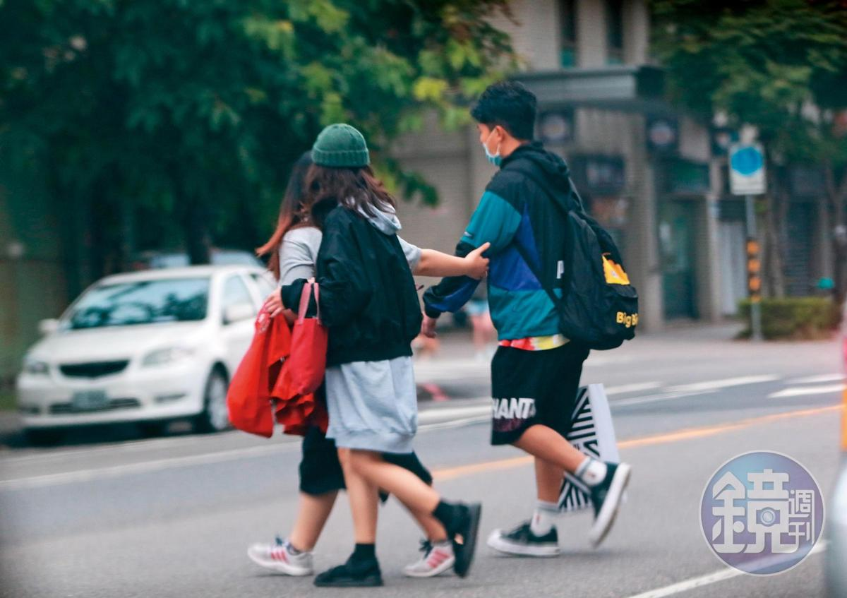 16:35 其中一名應該是經紀人,像保母似地拉著張立東(右)的手過馬路。