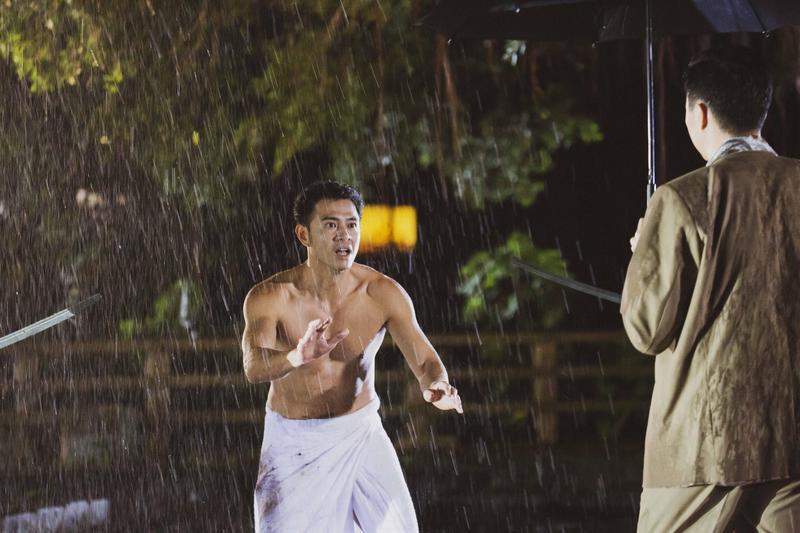 《苦力》其中一場戲,黃玉榮下身只披一條浴巾在大雨中遇吳鈴山尋仇,著急求饒模樣狼狽。(公視提供)