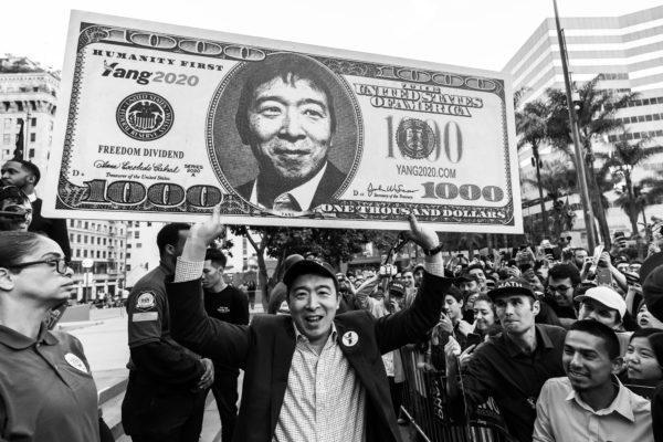 楊安澤高舉千元美元道具鈔票宣傳「自由津貼」政見。(yang2020.com)