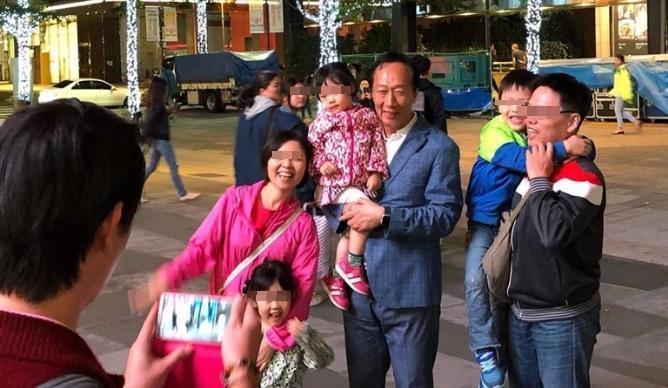 鴻海集團創辦人郭台銘吃完晚餐後現身信義區,熱情粉絲搶合照。(翻攝郭台銘粉絲團)
