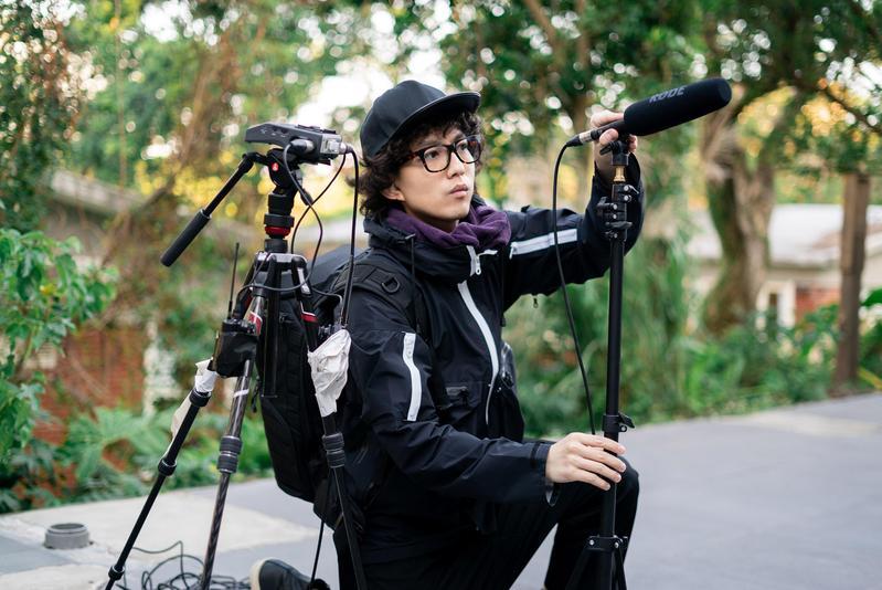 林宥嘉應社群論壇 Dcard之邀,戴上大捲髮、帽子與眼鏡,變身一日實習攝影助理。(華研國際提供)