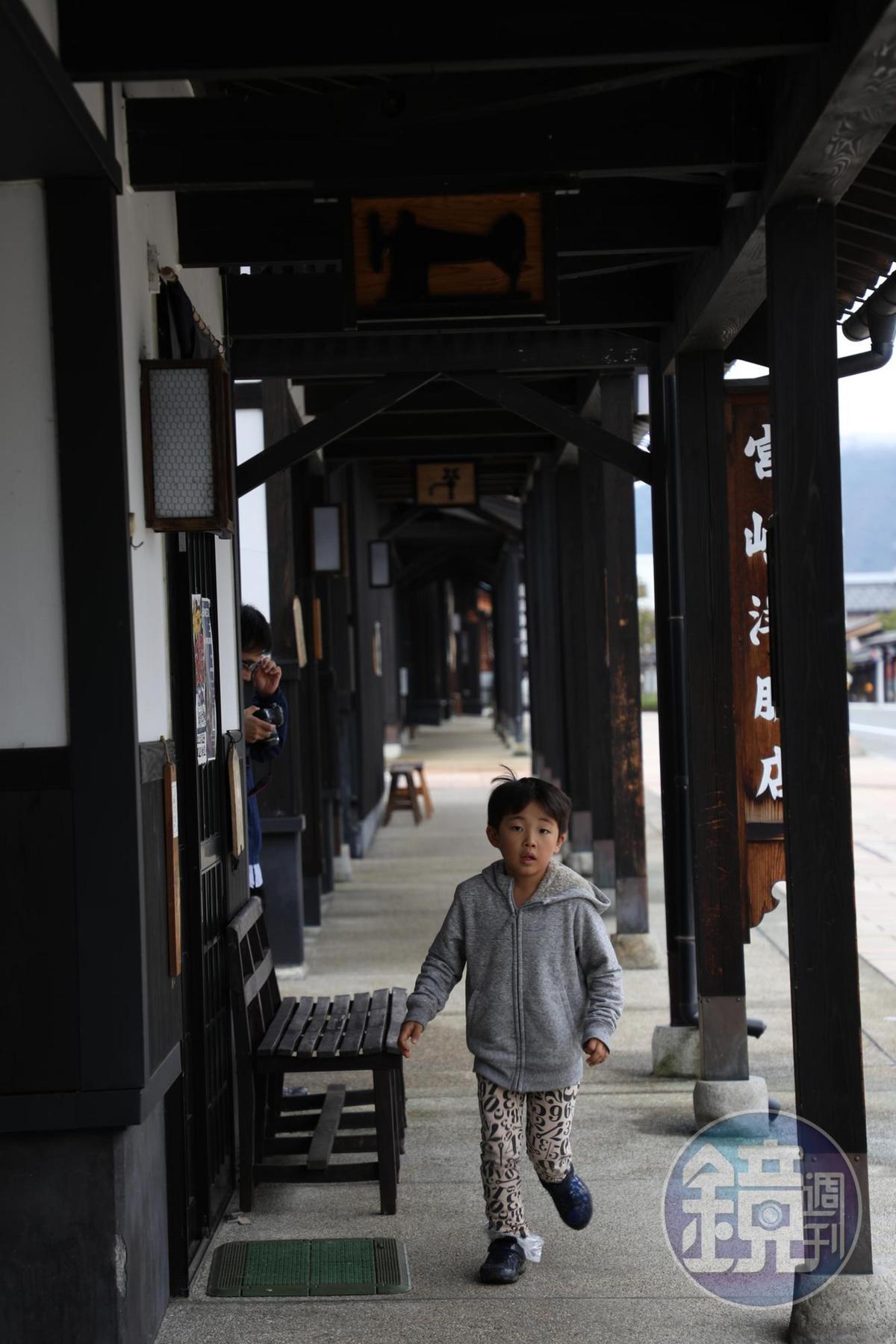 小男孩開心地在屋簷下奔跑玩耍。