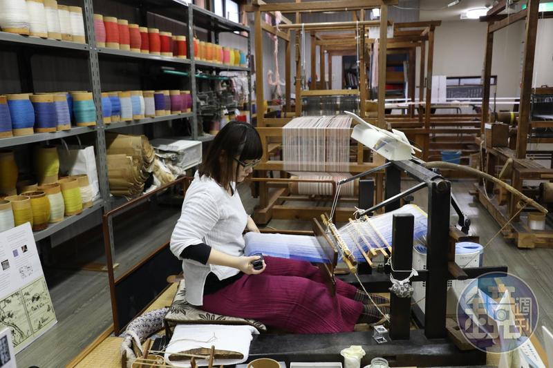 學習手工織布5年的丸山由貴菜,示範如何操作傳統織布機。