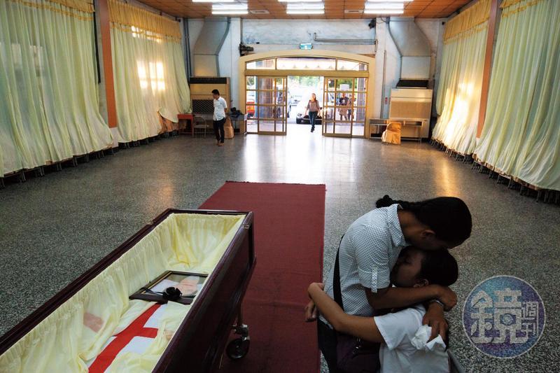 德希莉的遺體未火化,完整送回故鄉,三姊德娜(左)、七妹德琪(右)在棺木旁相擁痛哭。