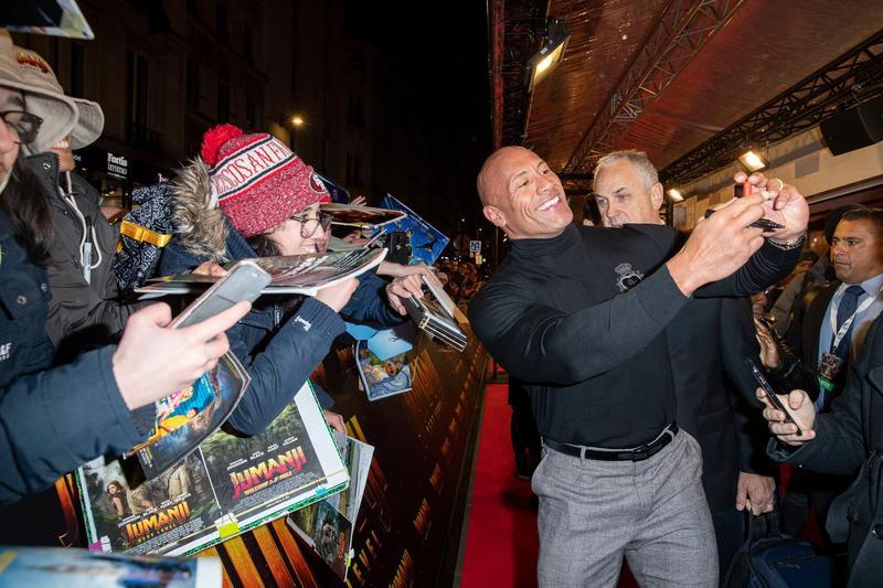 巨石強森人氣強強滾,在巴黎首映紅毯不停與影迷合照。(索尼提供)