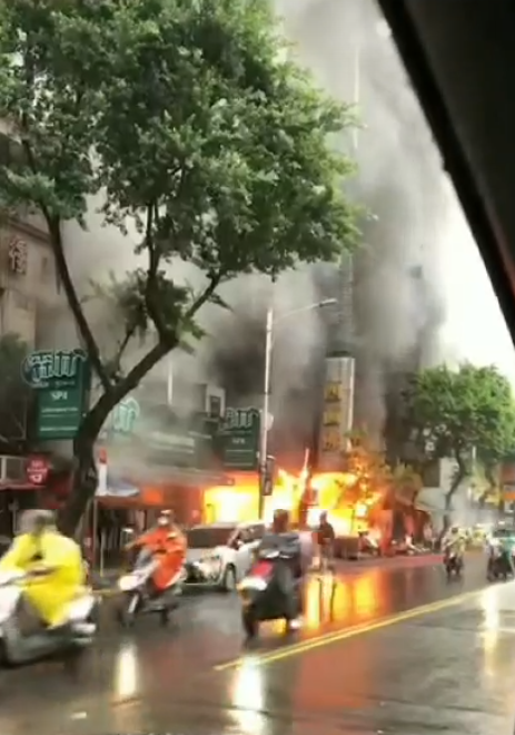 林森北路的四面佛寺遭一名雨衣男子縱火,火勢一發不可收拾。(翻攝畫面)