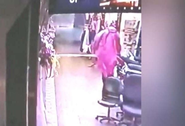 身穿粉紅色雨衣的不明人士,向四面佛廟潑灑汽油點火。(翻攝畫面)