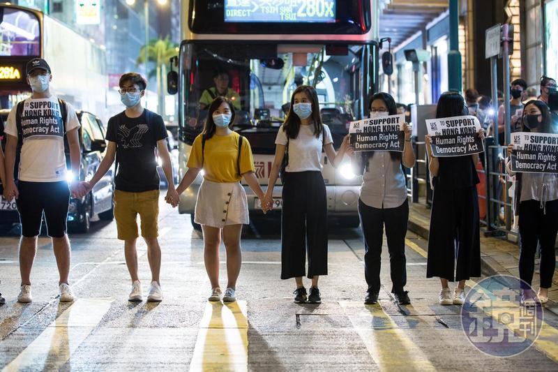 一名少女在人群中舉起「一疊白紙」抗議,遭香港警察以強光掃射臉部。(示意圖,非新聞當事人)