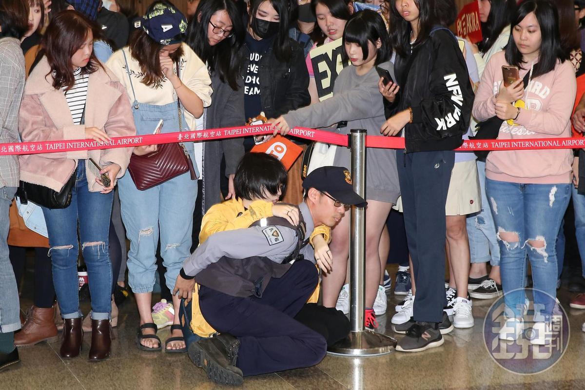 女粉絲疑似體力不支腿軟倒地,機場工作人員立刻前往協助。