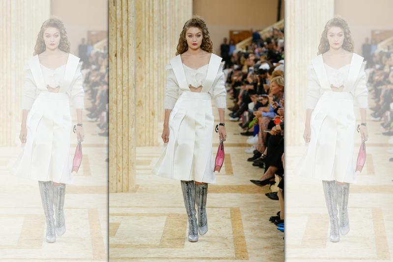 超模Gigi Hadid穿上感覺過小的不對稱毛衣,搭配學生感十足的吊帶裙,呈現粗獷與精緻的對比。(MIU MIU提供)