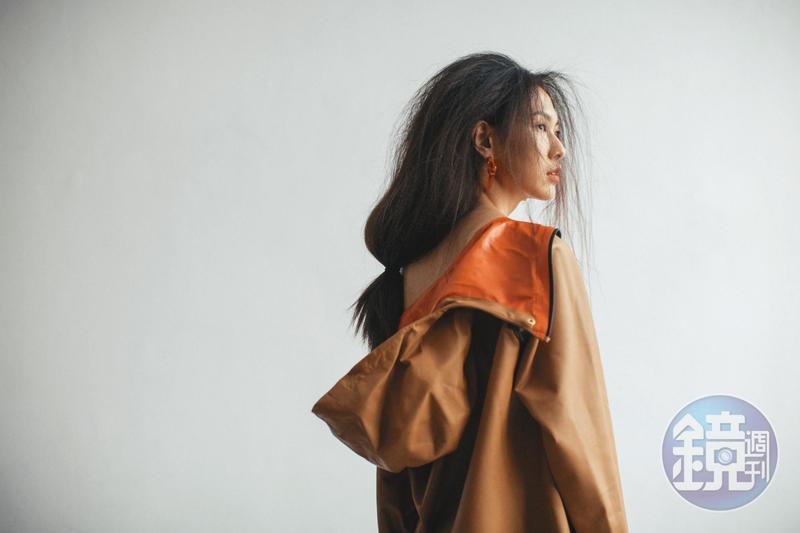 蜜糖棕小牛皮抽繩連帽洋裝 NT$237,500 by Bottega Veneta;設計耳環 NT$19,800 by FENDI。