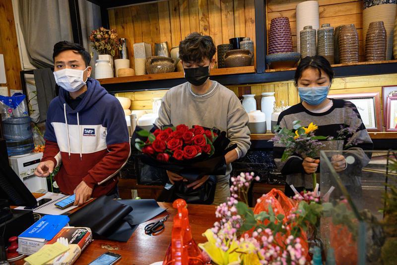 花店員工在情人節忙碌打包花束不忘防疫。(東方IC)