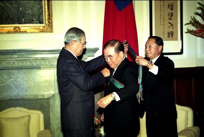 1993年2月26日,時任總統李登輝(左)頒勳章給當時即將卸任的行政院長郝柏村(中)。