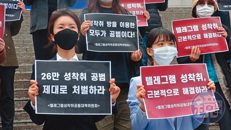 協助受害人打官司的朴藝安律師(左)及曹寅浩律師(右)。她們手持標語,訴求「好好處罰26萬名性剝削共犯」與「Telegram性剝削從根本解決」。
