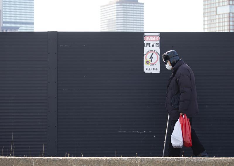 美國疫情封鎖期間,波士頓一名男子戴口罩走過空蕩無人的街道。(東方IC)
