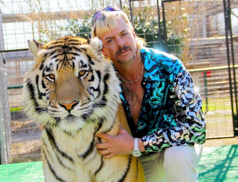 異國喬的髮型是狼尾頭,整個造型簡直比鄉土劇還要「WTF」。而且他拿來合照的老虎不是視力不佳,就是有打過麻醉劑,但他很會搞這套自我宣傳,讓人以為他真的有兩把刷子。 (Netflix提供)
