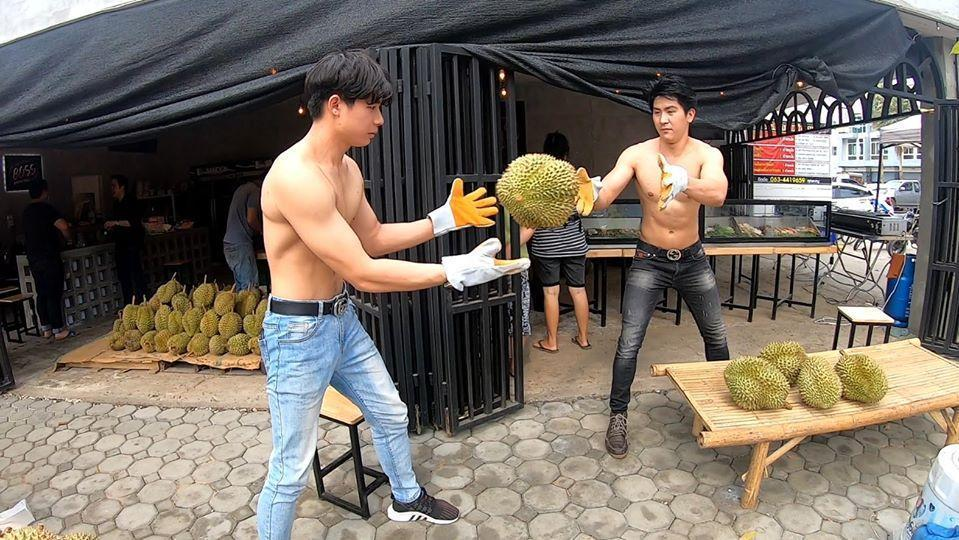 2名男子成了水果行的賣點,不過也有網友搞笑問,為什麼不戴口罩啊?(翻攝自「กูรู้..โลกรู้ 」粉絲頁)