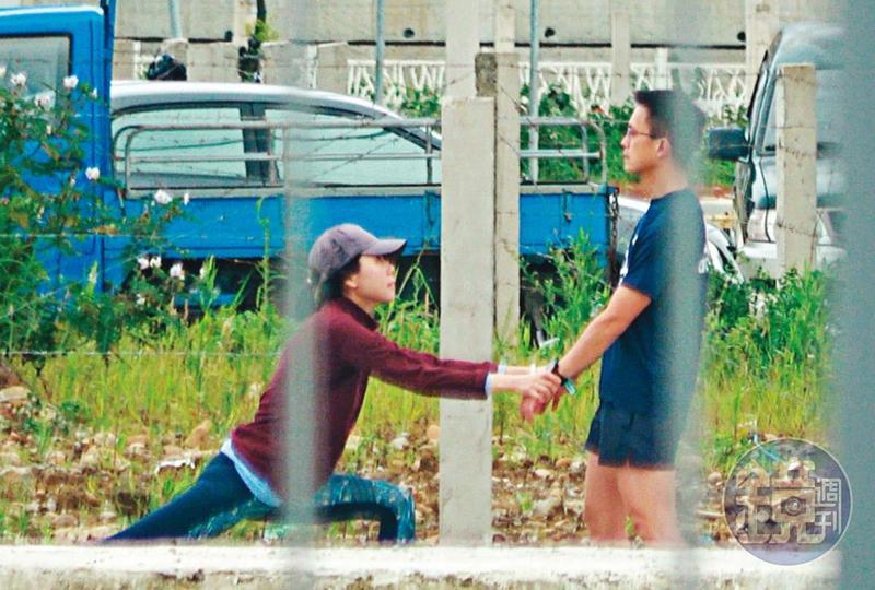 4/25  12 : 49,跑步前,吳彭弘(右)跟簡芳貞(左)先在路邊拉筋,2人拉著雙手,簡蹲下伸展下肢,整體看起來滑稽。