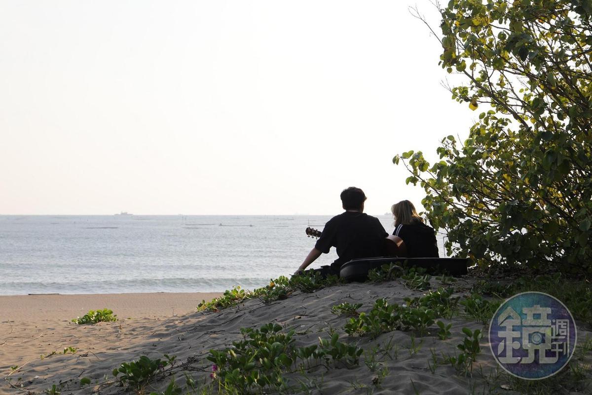 情侶們坐沙灉上自在談心。