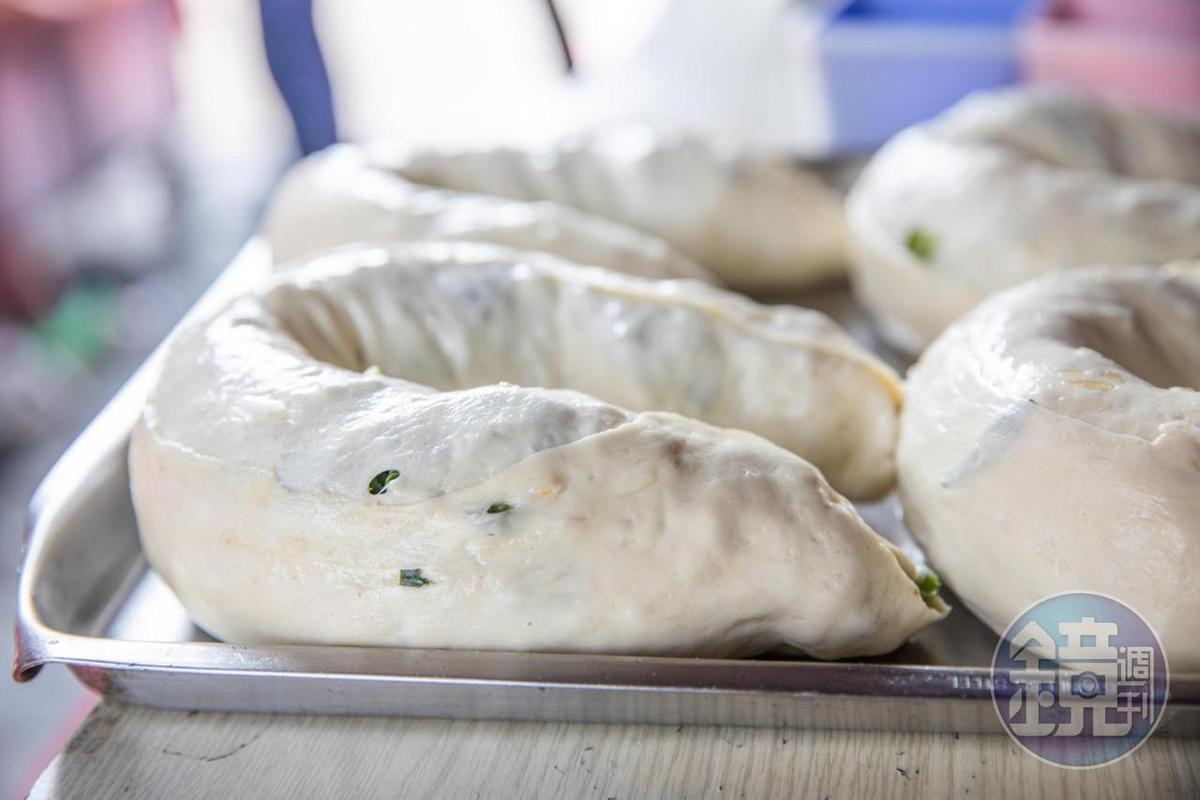 捲成柱狀的生蔥卷會先繞成圈型,準備下鍋煎香。