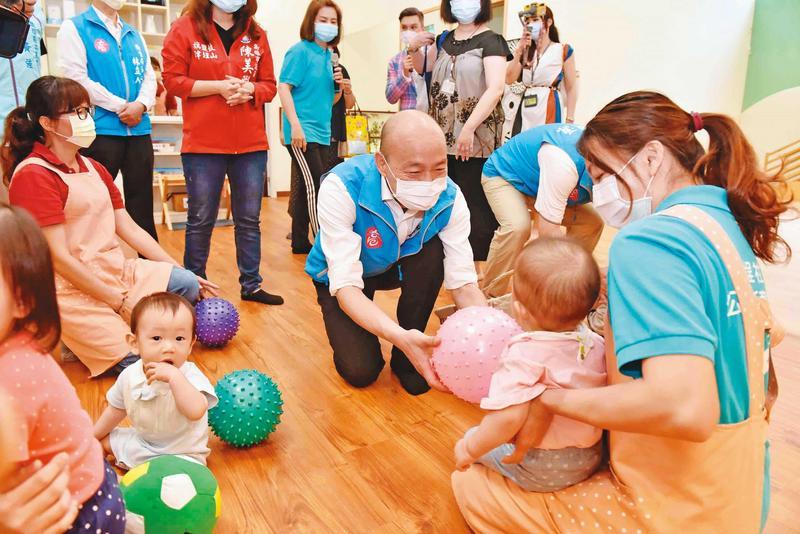 低調避戰的韓國瑜28日赴鹽埕公共托育家園揭牌、親近孩童,並開出7月提高托育人員薪資的承諾。(高雄市政府提供)
