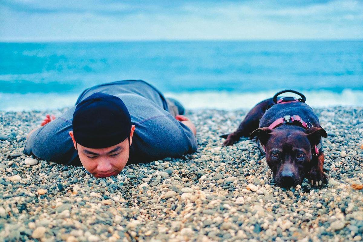 賴聖文帶著米菇環島,圖為去年4月一人一狗趴在花蓮七星潭留影。(賴聖文提供)