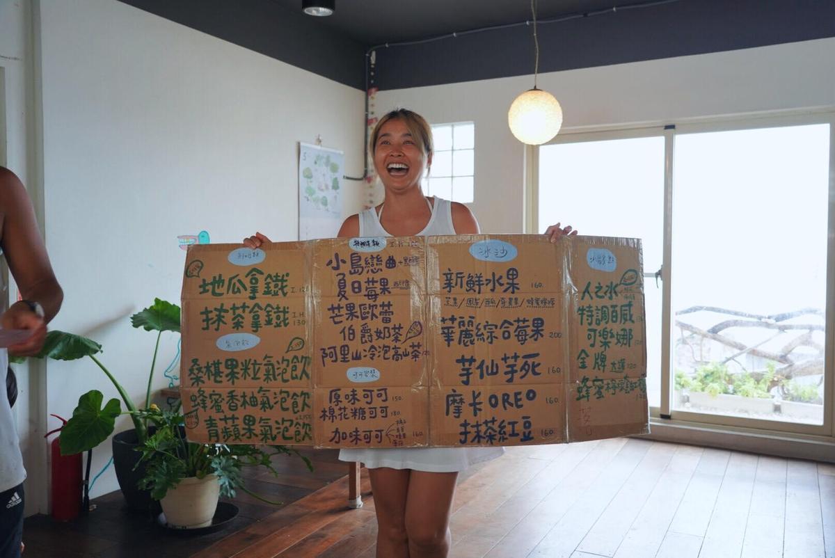 小嫻人在蘭嶼舉著飲料菜單紙牌,笑得非常燦爛。(翻攝自隋棠 Sonia Sui臉書)