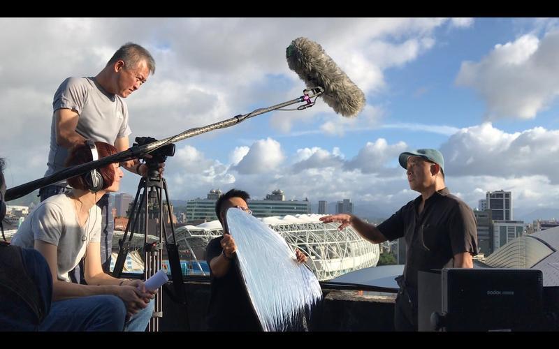 王婉柔(左前)訪問黃健和(右)時,攝影師韓允中(左後)想出在陽台拍攝的場景。(貝殼放大提供)