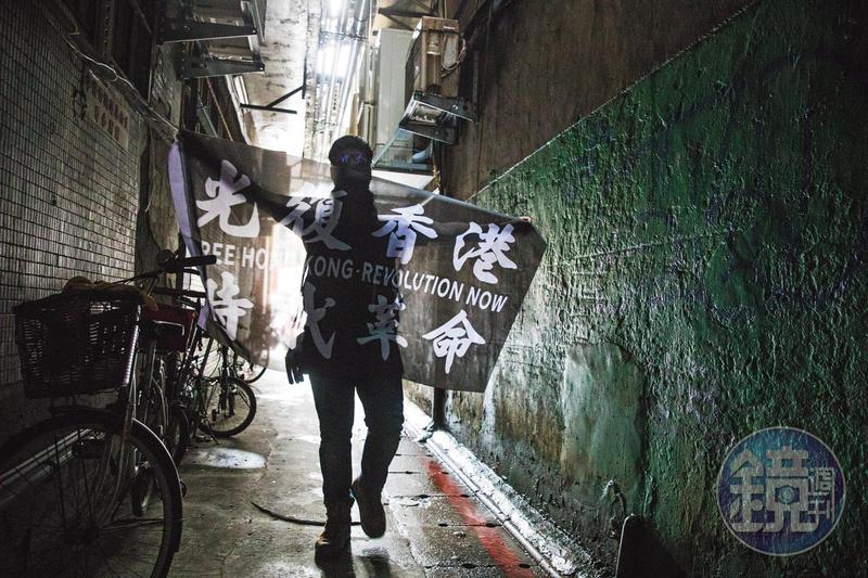 因反修例運動來台的港人中,不乏身分敏感者,他們自備面巾、頭套,全程蒙面受訪。圖為一名港人在台北的巷弄中,攤開自己設計、印製的「光復香港、時代革命」旗幟。