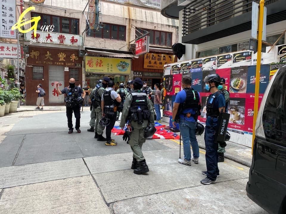 香港男子被警方搜身發現持有數面「中華民國」國旗,被依「涉嫌違反港區國安法」當場以警車載走。(翻攝自YKS至尊寶臉書)