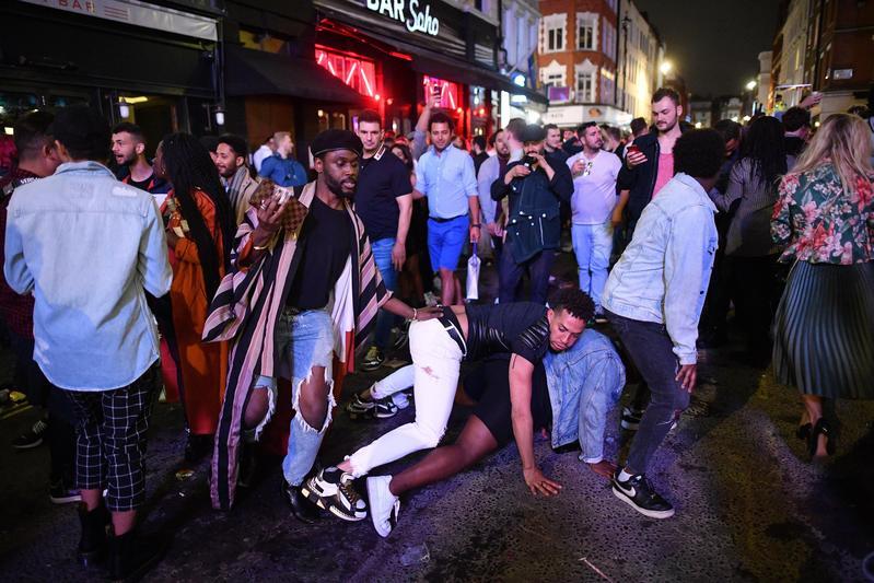 英國倫敦蘇活區湧入眾多酒客,卻也讓警察疲於奔命。(翻攝自推特@JustinTallis)