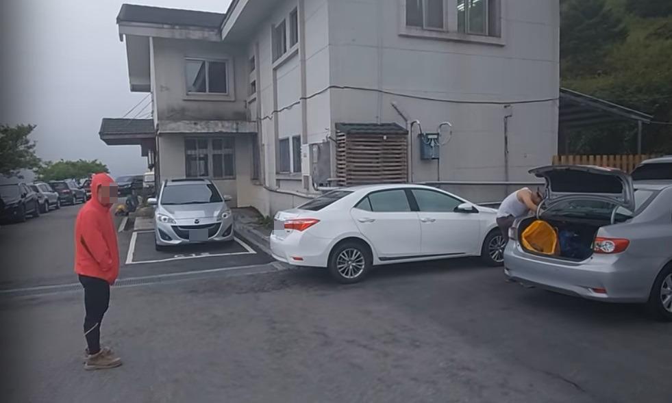 疑似與違停車輛駕駛同行的紅衣山友,在鏡頭前嗆聲。(翻攝自Youtube頻道Kris Loak)