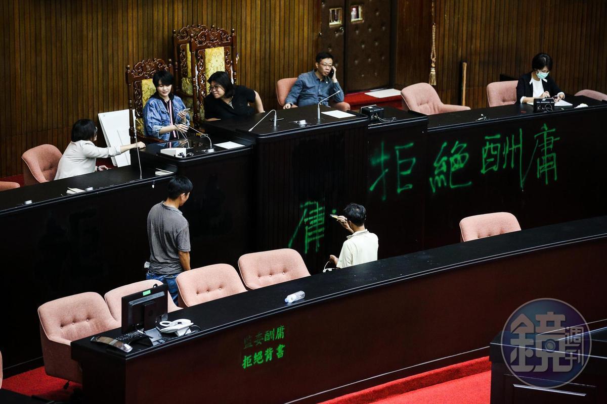 6月29日民進黨立委奪回議場後,工作人員修復議場被噴漆的主席台。