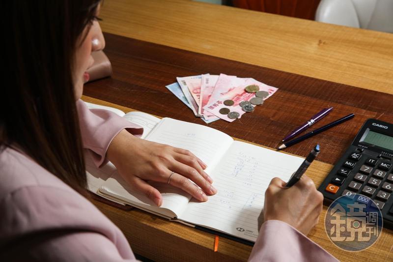 攤開錢包、倒出紙鈔與零錢,梁以辰仔細計算所剩金額,是否與記帳本數字相符。