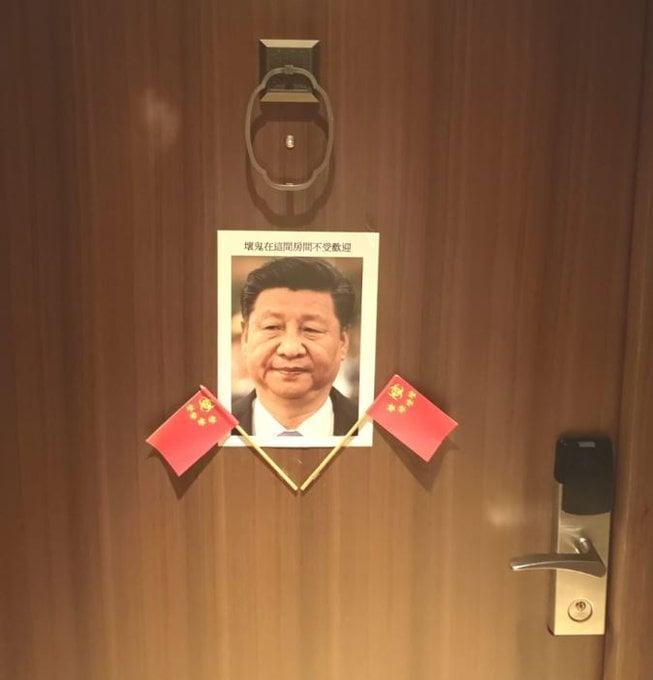 門上出現習近平肖像,還在下方插了兩支五星旗,照片上更以繁體字寫著「壞鬼在這間房間不受歡迎」。(翻攝自Lumír Aschenbrenner臉書)
